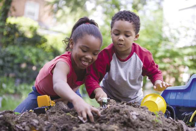A boy and a girl digging with their hands in a pile of dirt.
