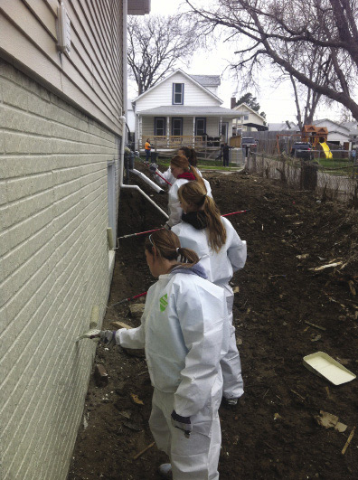 Volunteers in protective coveralls painting a house.