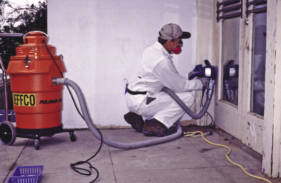 A worker in protective clothing and using a special sander to minimize lead-based paint exposure.