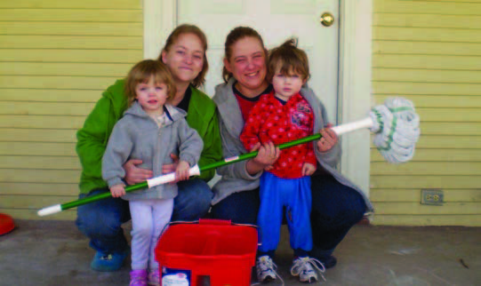 A mother and three girls sitting on their front stoop with a mop and cleaning materials.