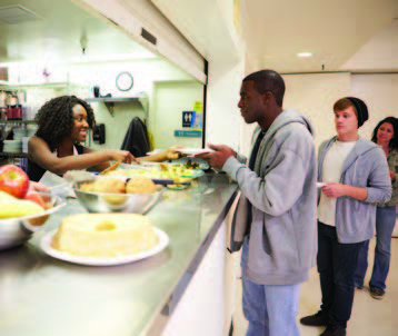 Homeless youth being served by food kitchen workers.