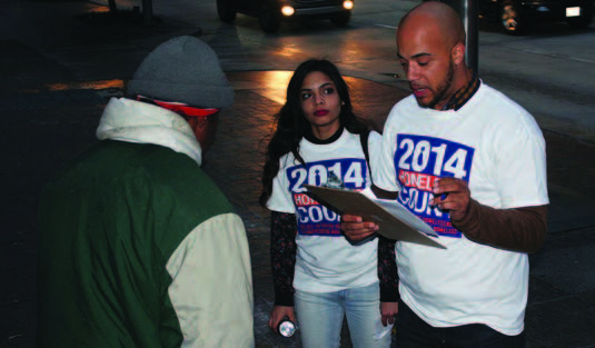 Two homelessness census takers interviewing a homeless man on the street at night.