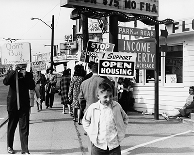 Protesters holding signs march at a demonstration in 1964 in Seattle, Washington.