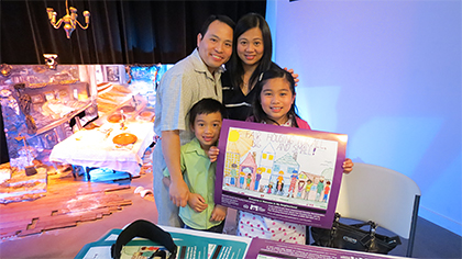 Samantha Tan, surrounded by her family, holds her poster which was the winning entry in the Fair Housing Council of Oregon sponsored poster contest.