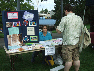 A table top display by the Northwest Fair Housing Alliance showing brochures, flyers, and other fair housing materials.