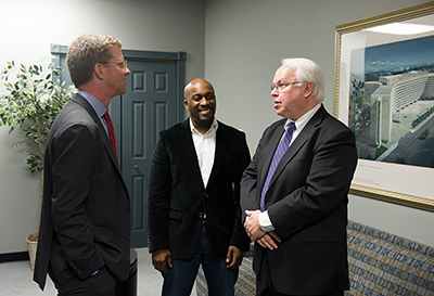 Photo shows HUD Secretary Shaun Donovan chatting with Steve Brady and Fred Freiberg.