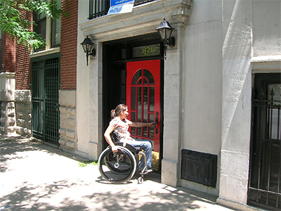 Woman in wheelchair opening the door to a multifamily building.