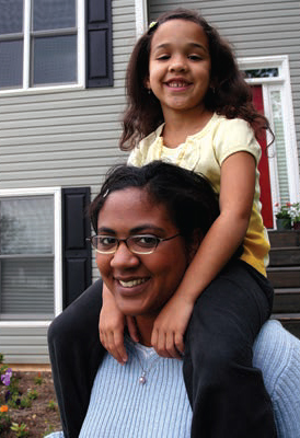 A mother and daughter pose in front of a home.
