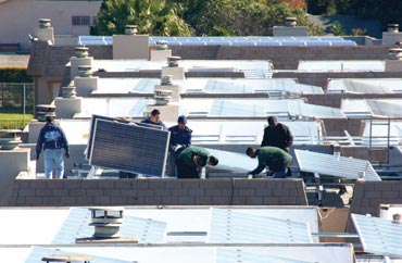 Image of Young adults from the YouthBuild program equip multifamily housing buildings with solar panels while learning to install the new technology.
