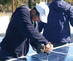 Hector del Real, a former YouthBuild job trainee shown here installing solar panels on a multifamily retrofit, is now a full-time employee with Everyday Energy in one of the new kinds of jobs generated by clean energy initiatives.