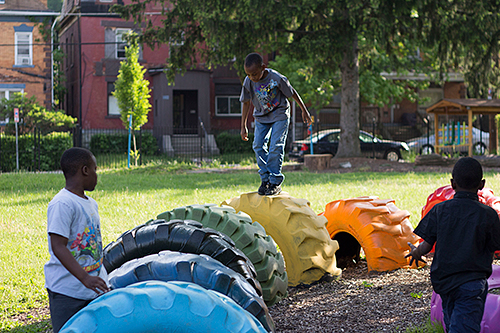 A greened and repurposed vacant lot, converted to a play area in which children are shown playing.