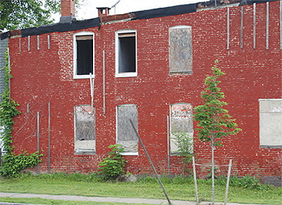 A brick building in deteriorating condition with boarded up and broken windows.