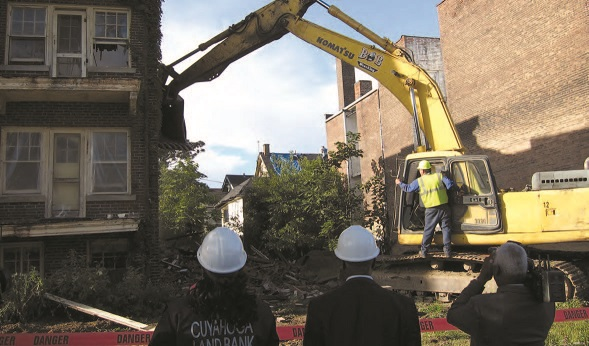 A work crew in hardhats operating heavy equipment to demolish a vacant, abandoned brick apartment building.