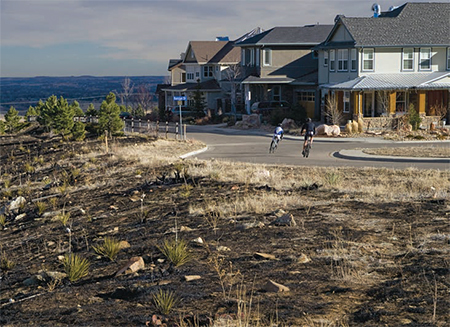 A road circling a Colorado subdivision separates houses from fire damaged land.