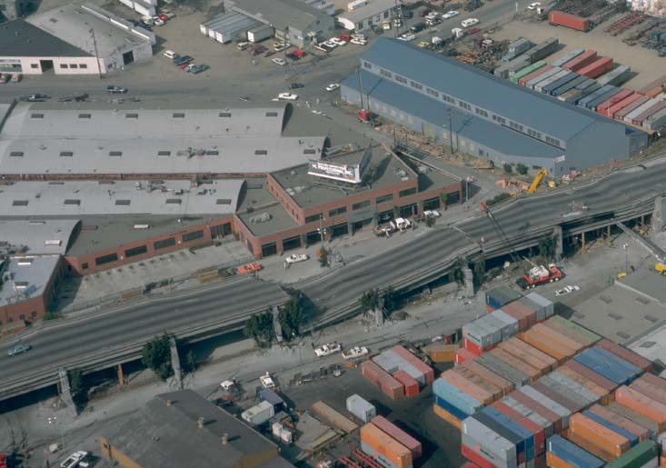 An aerial view of a double-decked freeway viaduct showing the upper deck collapsed onto the deck below.