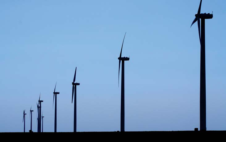 A row of wind generators spread across a field, backlighted by the sky.