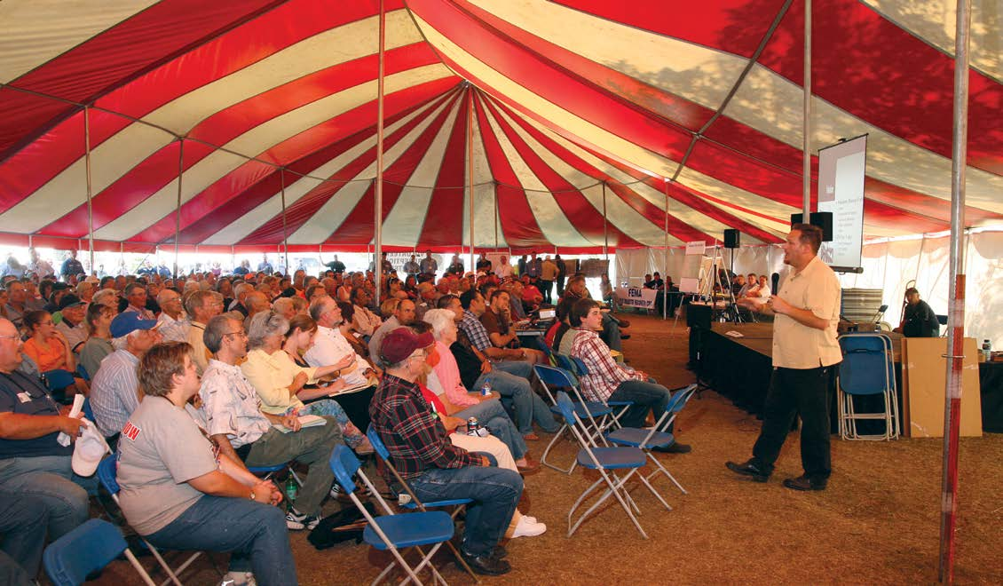 A group of people seated on folding chairs in a tent, listening to a speaker.