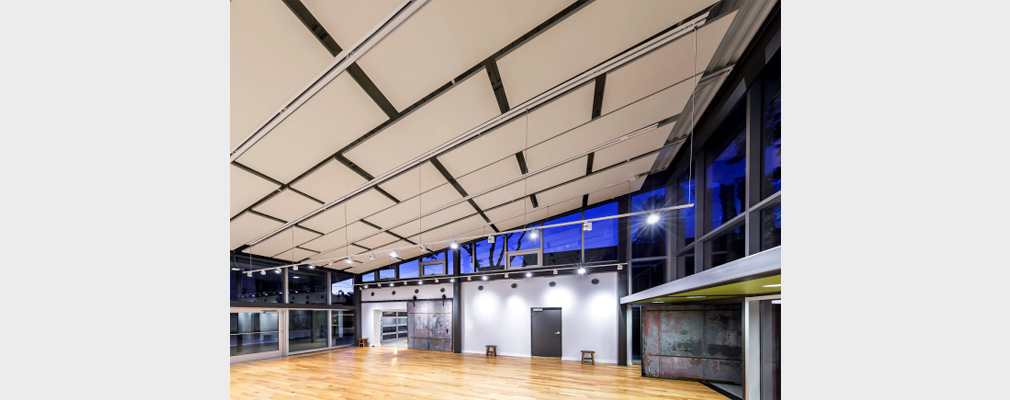 Photograph of interior of a large two-story performance space with a wooden floor and a slanted ceiling covered in specially crafted pads.