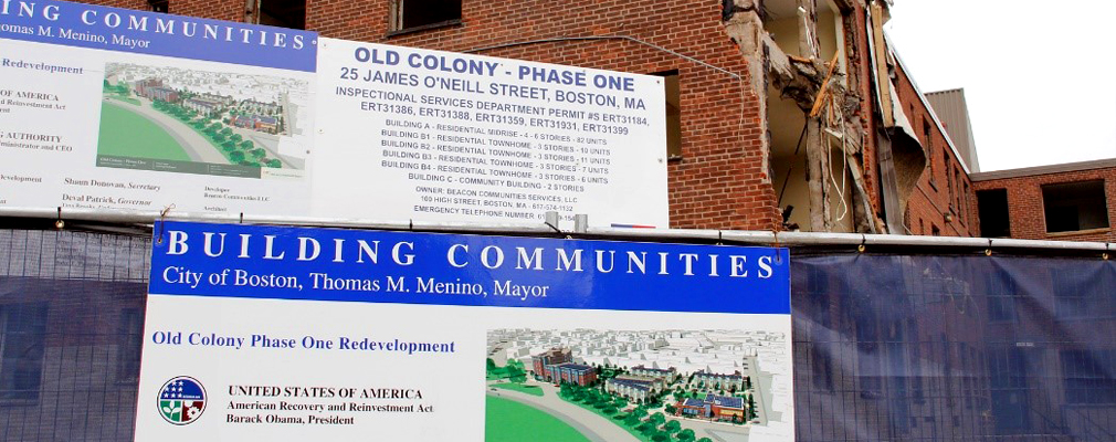 Photograph of a partially demolished multistory brick building with two large signs in the foreground detailing the redevelopment plans for Old Colony Homes Phase I.