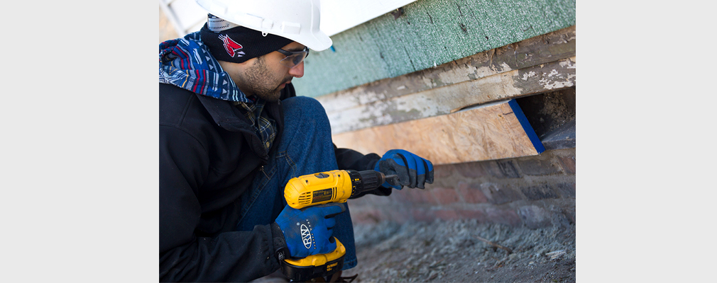 Photograph of a young man using an electric drill on the wood sheathing of a building.