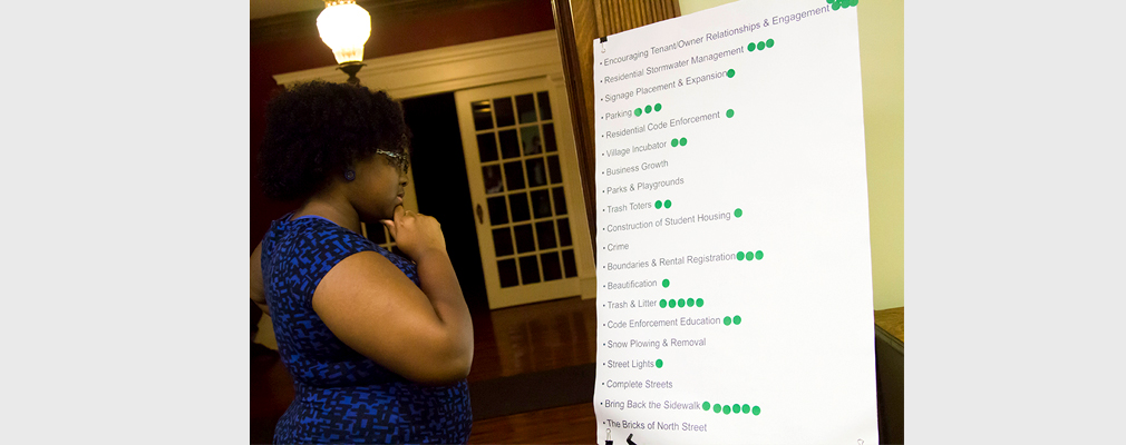 A woman looks at a poster-sized list of projects that residents have used to indicate their preferred neighborhood improvement projects.