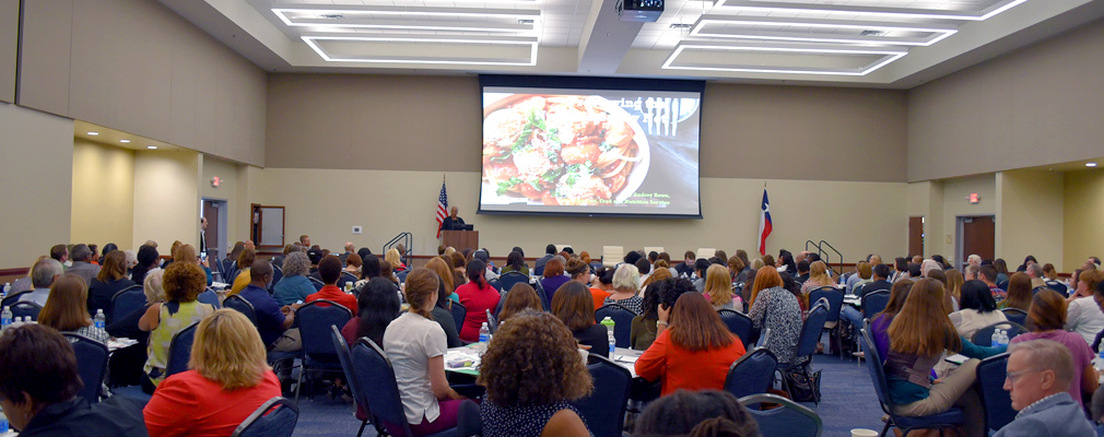 Photograph of dozens of attendees at the 2016 Dallas Hunger Summit seated at tables in a large meeting room and watching a presentation.