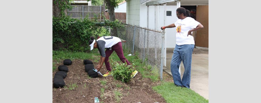 Photograph of two volunteers working in a backyard vegetable garden.