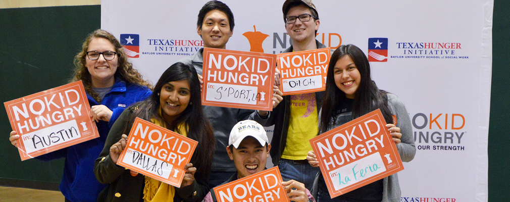Photograph of six No Kid Hungry campaign volunteers holding signs identifying their respective cities: Austin, Dallas, Shreveport, La Feria, and Oil City.