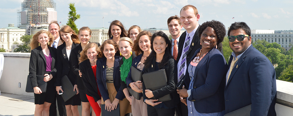 Photograph of 15 students and faculty with the capitol in the background.