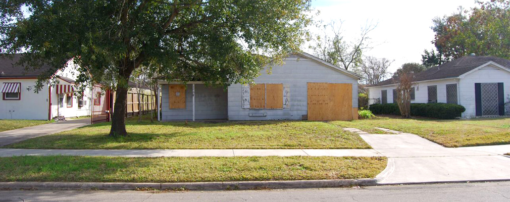 Photograph of the front façade of a boarded-up single-family house damaged by Hurricane Ike.