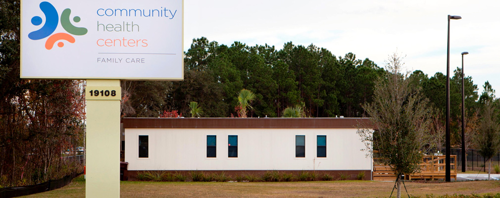 "Photograph of a side façade of a modular building with a wooden accessibility ramp behind a sign which reads ""Community Health Centers Family Care."""