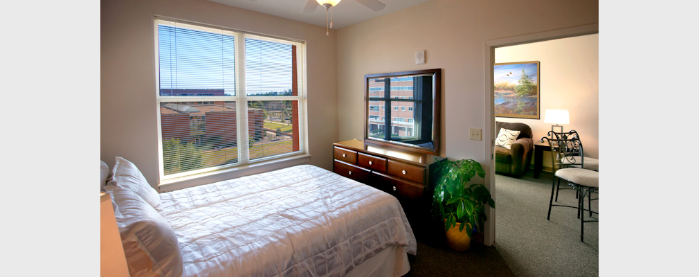 Photograph of the interior of a bedroom with a doorway opening into the living room and window overlooking a university building.