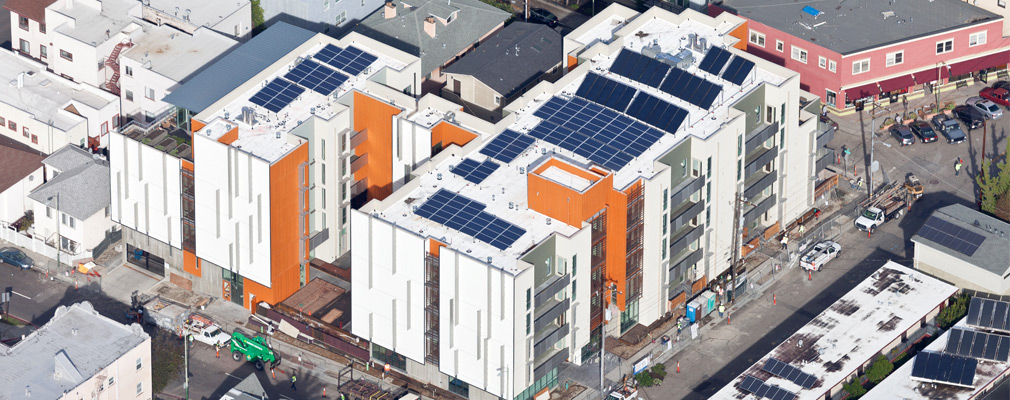 A top view of a nearly-complete five-story apartment building, topped with banks of solar panels.