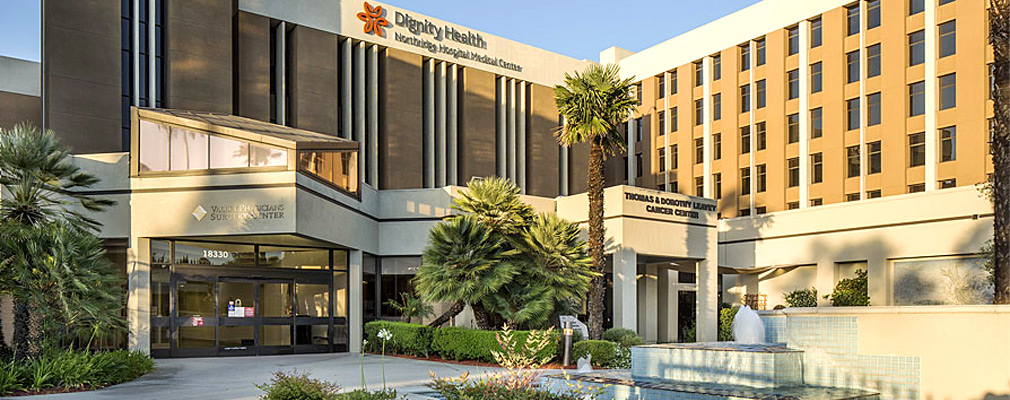 "Photograph of the front façade of a six-story institutional building with a sign that reads ""Dignity Health Northridge Hospital Medical Center."""
