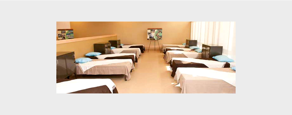 Photograph of 10 beds arranged in 2 rows in a large room.