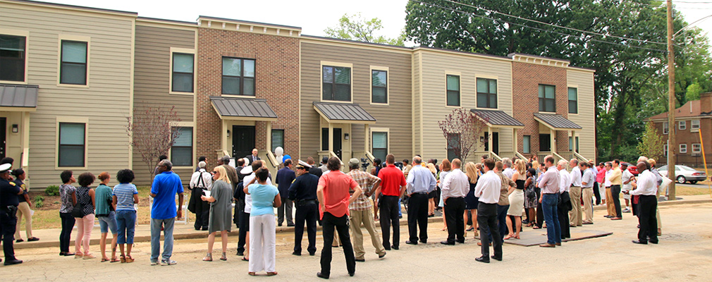 Photograph of a crowd of community members standing in front of five new two-story townhouses.
