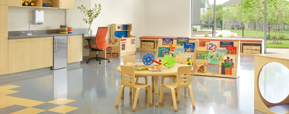 Photograph of the interior of a classroom containing a table and four chairs, a book display, and play equipment, with a landscaped play area beyond large windows in the back wall.