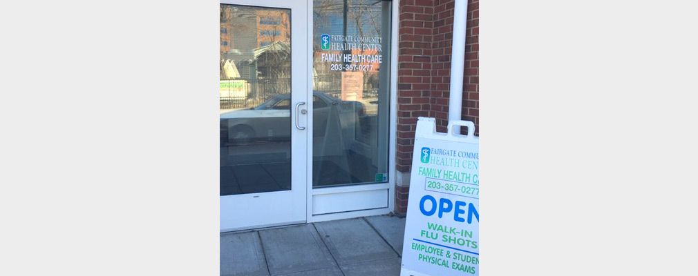 "Photograph of the glazed entrance to a brick office with a window sign reading ""Fairgate Community Health Center, Family Health Care"" and with a sandwich board sign on the sidewalk advertising available services."