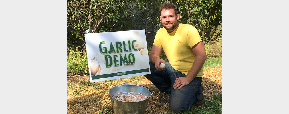 "Photograph of a man kneeling next to a pail full of garlic bulbs, in front of a sign reading ""Garlic Demo."""
