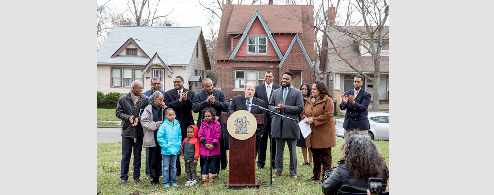 Photograph of a man standing at a podium speaking into a microphone with several adults and children standing nearby; three single-family detached houses are in the background.