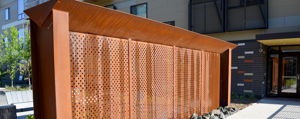 Photograph of a wall made of a perforated metal sheet, marked with vertical bands of condensed water, standing in a courtyard with a multistory residential building in the background.