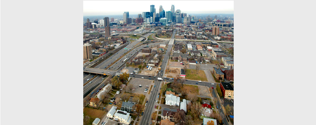 Low-altitude aerial photograph centered on an intersection of multilane streets, with downtown Minneapolis in the middleground.