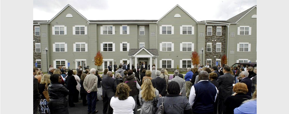 Photograph of a large group of people at a ribbon-cutting ceremony for a three-story apartment building in the background.