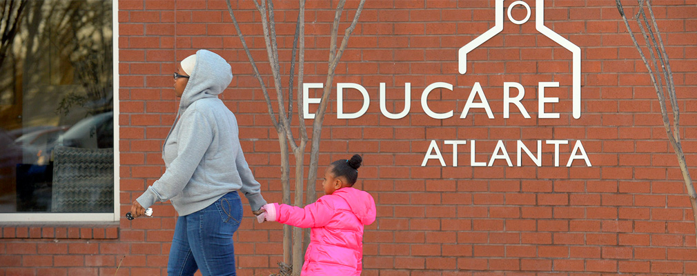 "Photograph of a child holding her mother's hand as they walk in front of a building with the sign ""Educare Atlanta."""