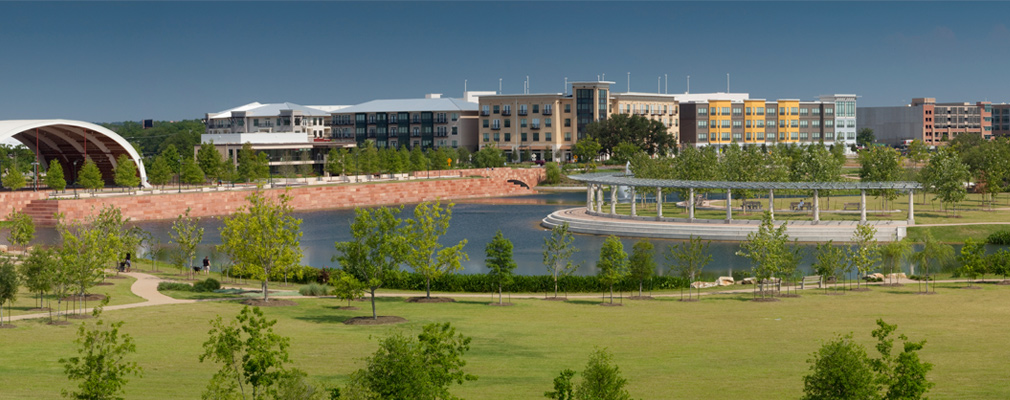 Panoramic photograph of a lake and park with residential and nonresidential buildings in the background.