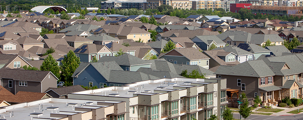 Photograph taken at roof height of townhouses and single-family detached houses, with multifamily housing in the background.