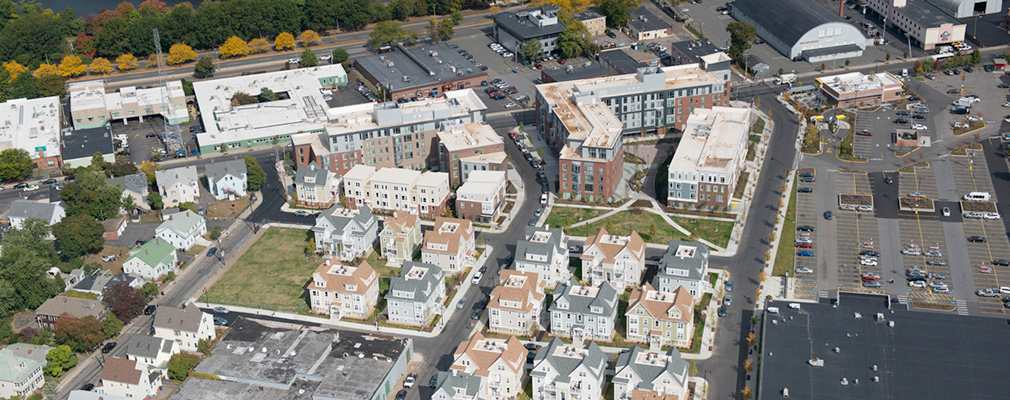 Low-angle aerial photograph of the development within the neighborhood context.