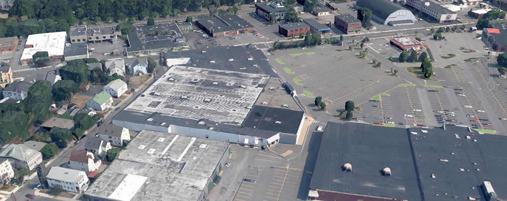 Low-angle aerial photograph of a shopping center on a large block bordered by commercial developments and residences.