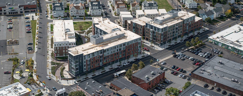 Low-angle aerial photograph showing the development — two 5-story mixed-use buildings, two 4-story apartment buildings, and several town homes — in the context of primarily 2-story commercial buildings and residences.