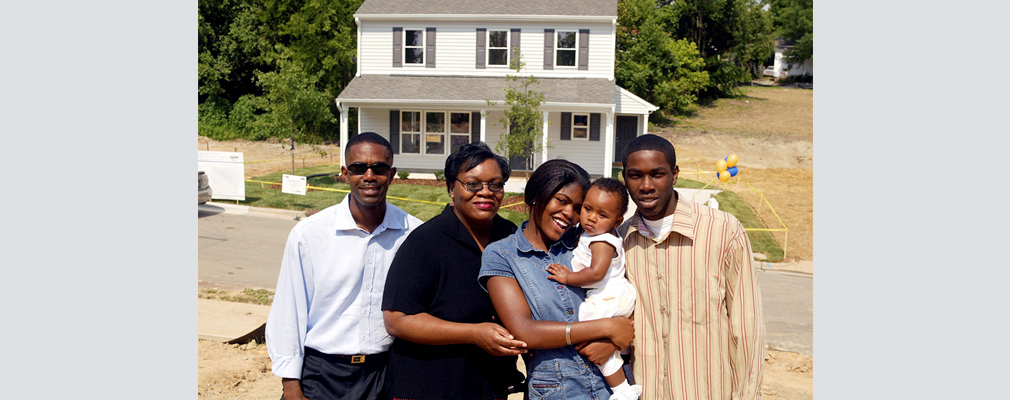 Photograph of four adults and an infant in front of a newly constructed two-story single-family detached house.